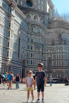 Two children stand in front of the Duomo cathedral in Florence