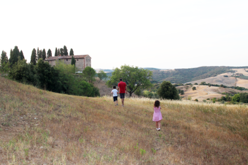 A family explore the grounds of their Airbnb accommodation in La Farneta, Tuscany, Italy.