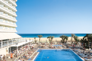 One of the pools at the Riu Oliva Beach hotel, with the beach behind