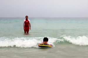 A boy bodyboards in the sea on Corralejo beach in front of the ClubHotel Riu Oliva Beach Resort.