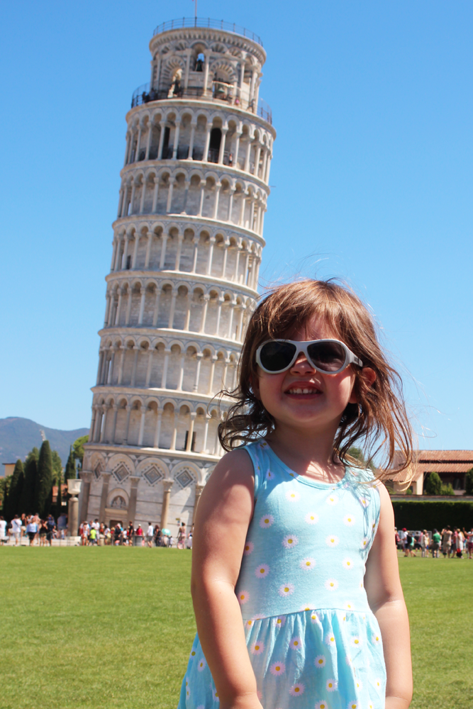 A toddler girl in sunglasses smiles in front of the Leaning Tower of Pisa in Italy.