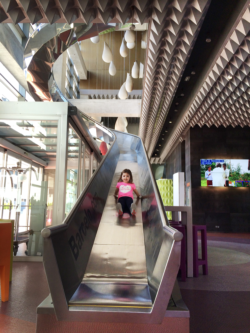 A girl takes the slide at Barceló Málaga hotel to get to receptiona