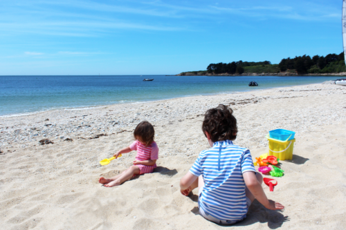 Two children play with buckets and spades on the beach at Port du Crouesty