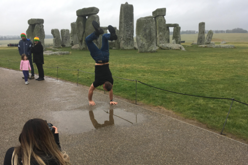 A visitor does a handstand in front of the stones at Stonehenge
