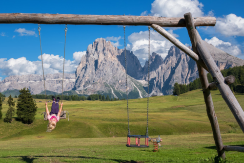 A child swings in a playground with the mountains in the background