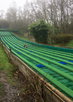 A child sledges down the slope of the Great Green Run