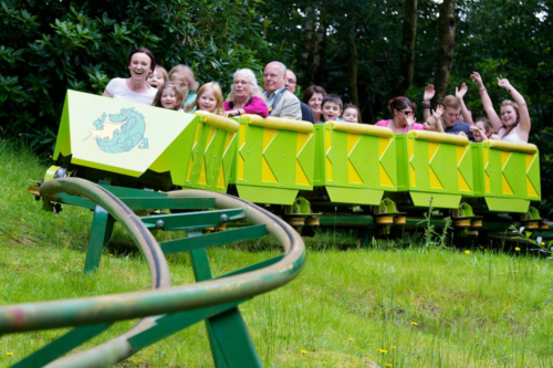 Children and families ride the Green Dragon Roller coaster