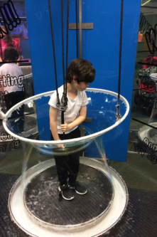 A boy makes a big bubble around him