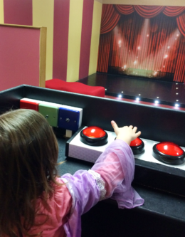 A girl presses buttons to control the stage lights and sounds