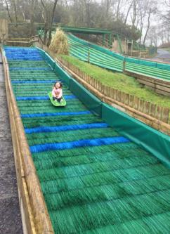 A girl rides a sledge down The Little Green Run