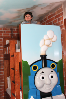 A boy looks over the top of his Thomas bed at Drayton Manor Hotel
