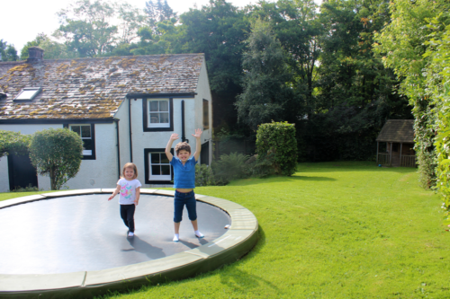 children on a trampoline outside a cottage