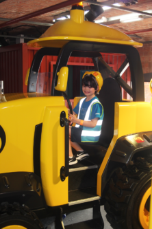 A boy sits in Scoop the digger