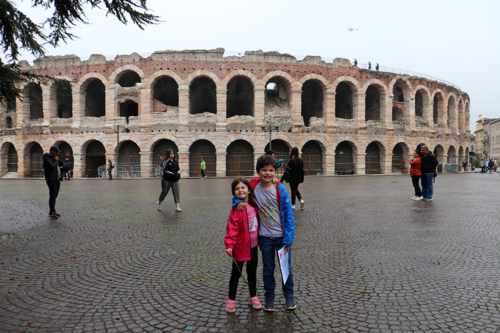 Two children outside the Arena amphitheatre in Verona, Italy