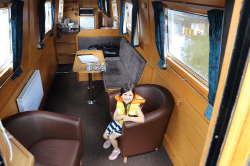 A girl sits in the lounge of the bond boat Askrigg from Anglo Welsh