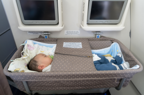A baby sleeps in a bassinet on an aeroplane