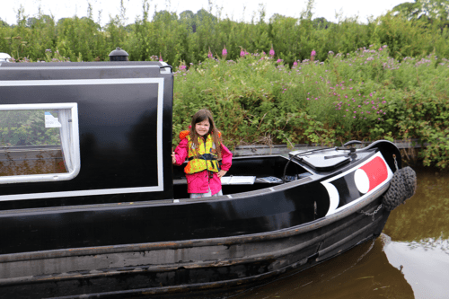 A girl wears a life jacket life vest on a canal narrowboat