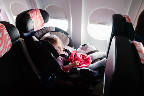 A child sleeps in a car seat on a plane by the window