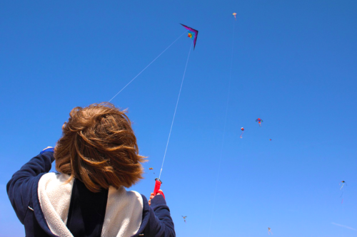 child flying a kite in a blue sky