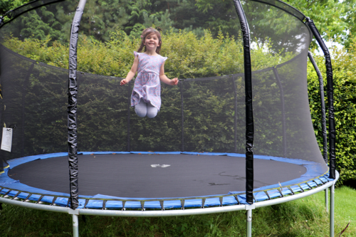 A girl jumps on a trampoline at Heath Farm Cottages