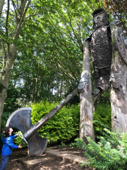 A boy looks up at a giant woodcutter statue at the Forbidden Corner