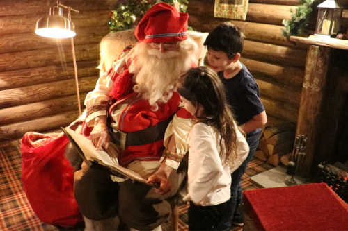 Children look to see if they are in Santa's good book at Lapland UK