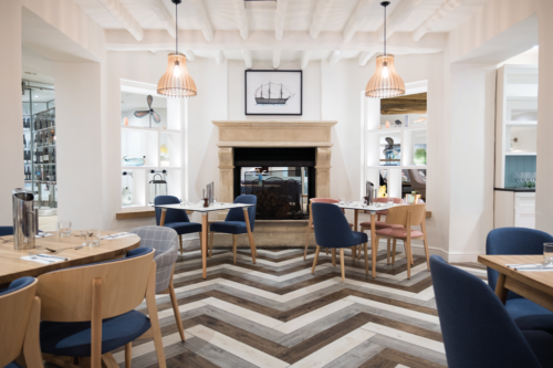 Dining tables, chairs and a fire at the Solent Hotel & Spa