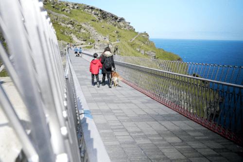 A family cross the Tintagel Castle bridge