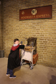A boy pushes his trolley through the wall on platform 9 3/4 at Harry Potter Studios in London