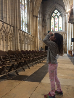 A girl uses binocular to look for items off a treasure trail inside York Minster cathedral.